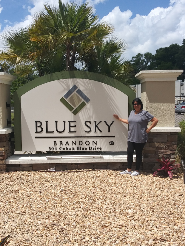 Haydee standing in front of the Blue Sky Brandon sign